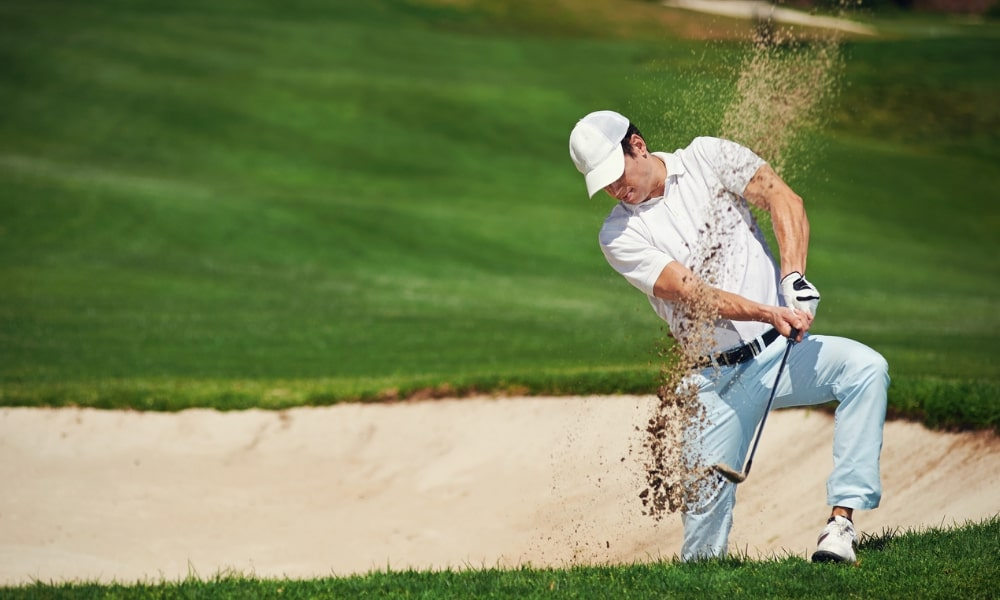 Golfer playing shot out of bunker