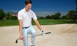 Golfer breaking club on knee