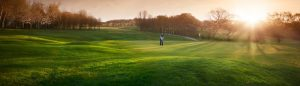 Golfer putting as the sun goes down
