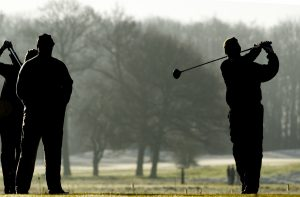 Three people playing golf in the winter